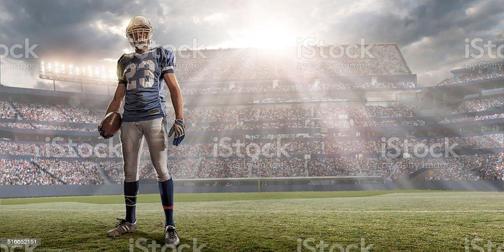 American Football Player in Sunlit Stadium stock photo