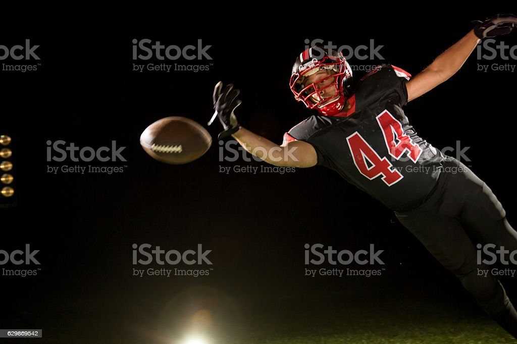 American football player jumping in air stock photo