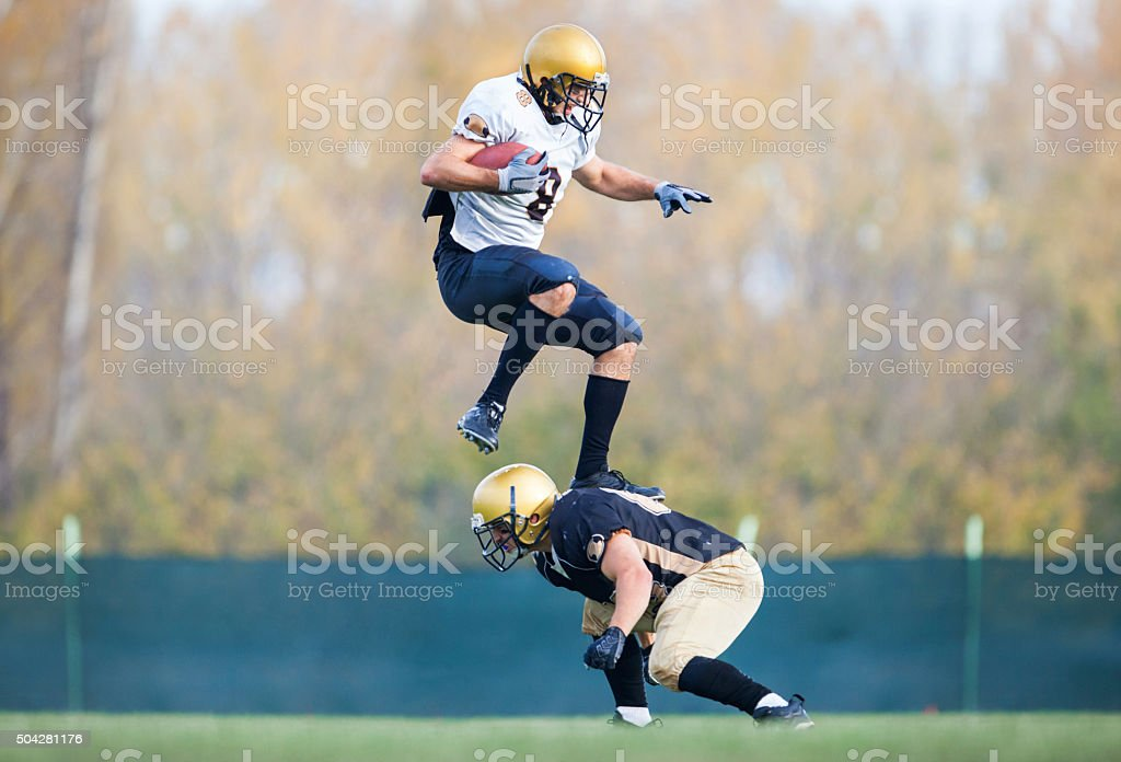American football player jumping over his opponent during a match. stock photo