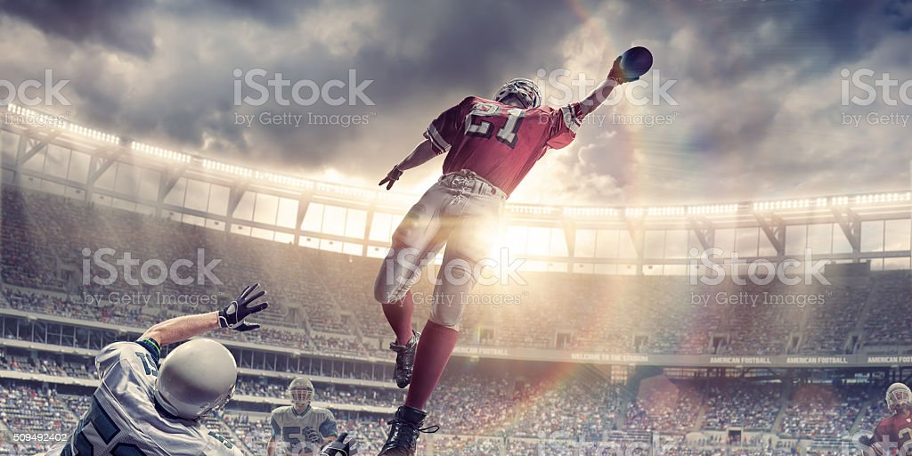 American Football Player Jumps to Catch Ball During Game stock photo