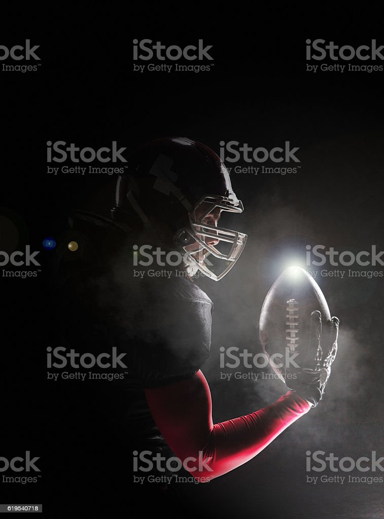 American football player posing with ball on black background stock photo