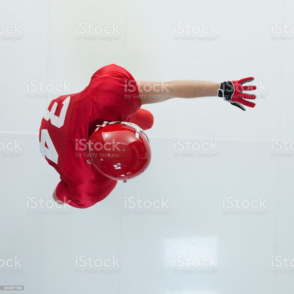 American football player pushing away opponents stock photo