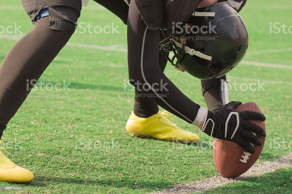 American football player setting up to snap the ball stock photo