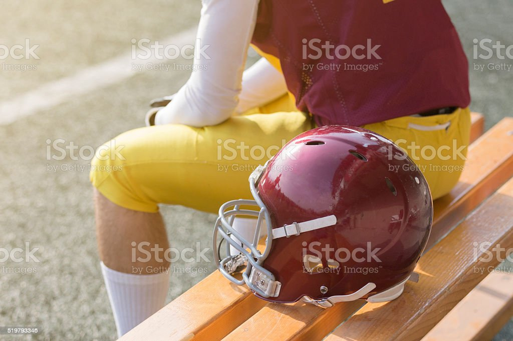 American football player sitting on bench next to sports helmet stock photo