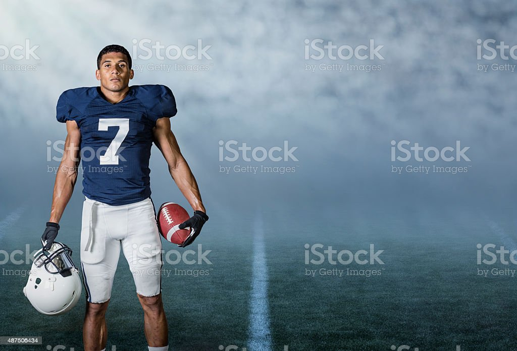 American Football player standing in a stadium at night stock photo