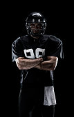American football player standing with arms crossed
