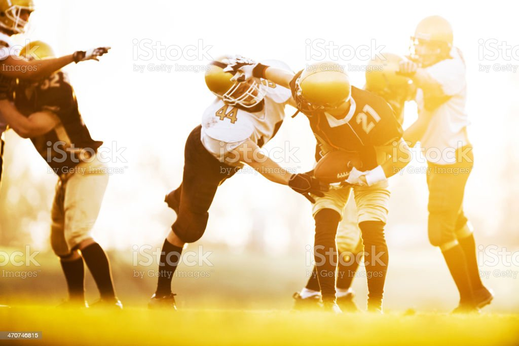 American football players in action at sunset. stock photo