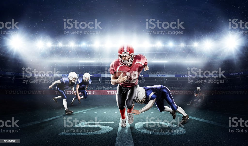 American football players in action on stadium with ball stock photo