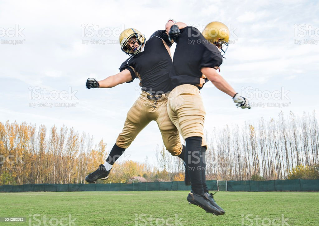 American football players jumping and confronting during a match. stock photo