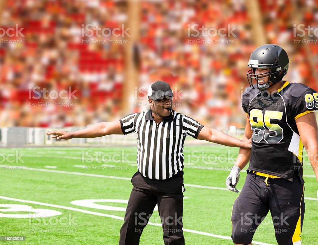 American football referee signals a play during the game. Player. stock photo