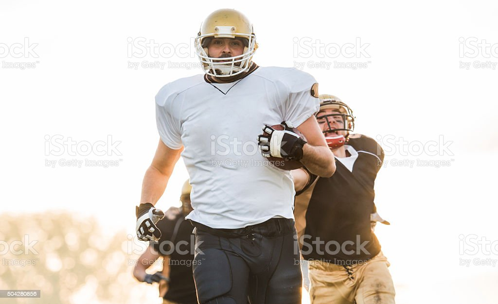 American football running from opponents with ball in his hands. stock photo