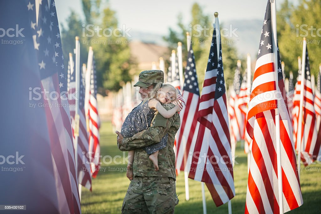 American girl hugging her dad in front of American flags stock photo