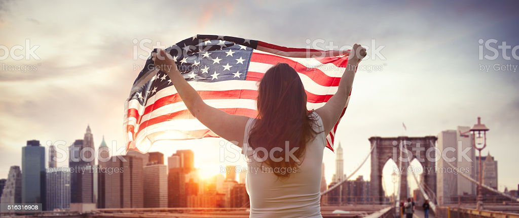 American girl with us flag on Brooklyn bridge in NYC stock photo