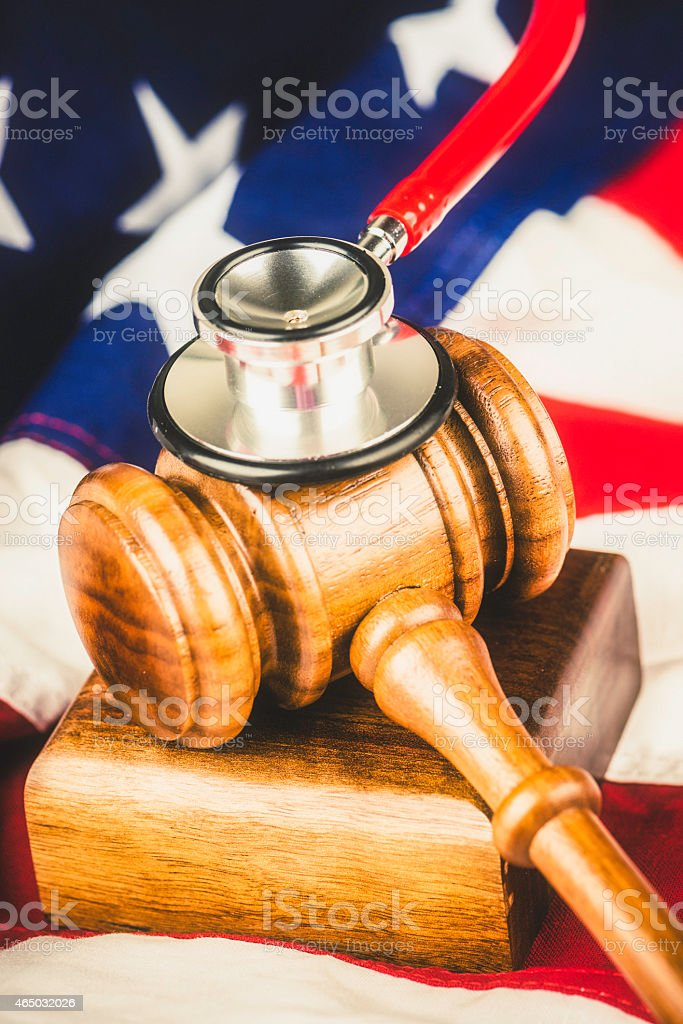 American Healthcare Malpractice Concept. Gavel, stethoscope and American flag. stock photo