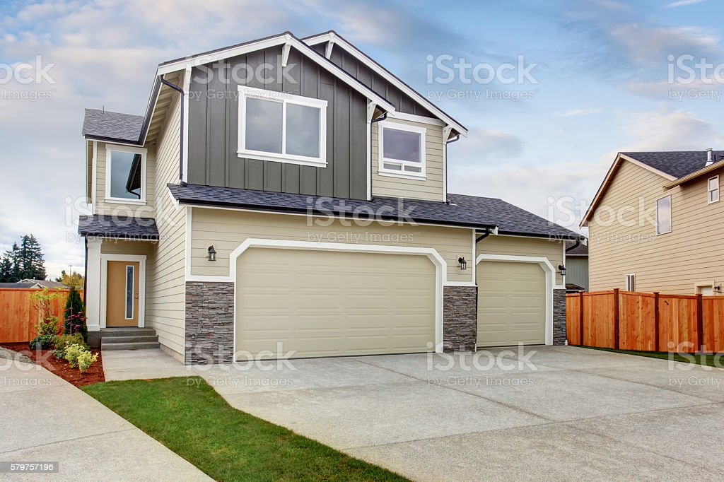 American house exterior with two garage spaces, concrete floor driveway. stock photo