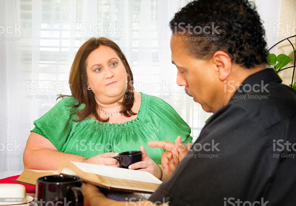American housewife listening to Christian evangelist reading the Bible stock photo