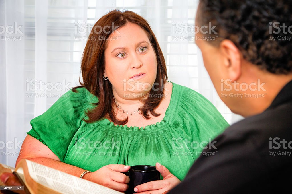 American housewife listens attentively while pastor reads her Bible stock photo