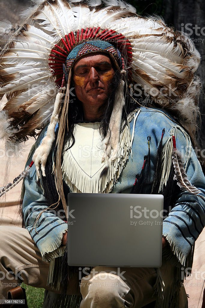 American Indian Man Wearing Traditional Dress and Using Laptop stock photo