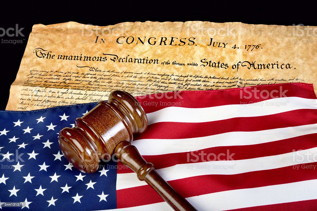 Declaration of Independence with American flag and wooden gavel.