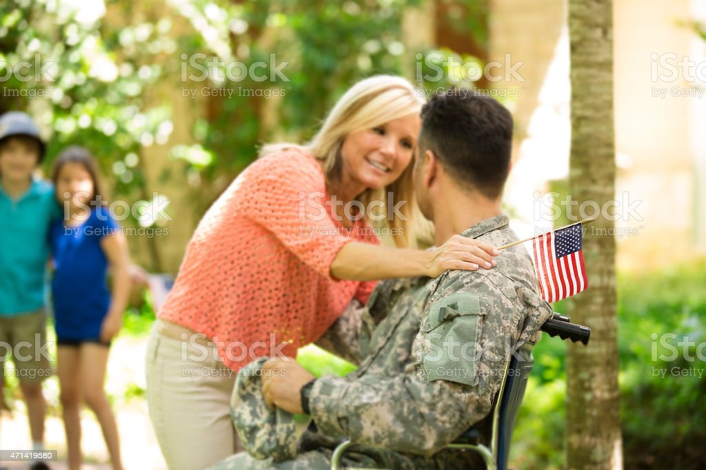 American military veteran welcomed home by family. Wheelchair, disabled. Home. stock photo