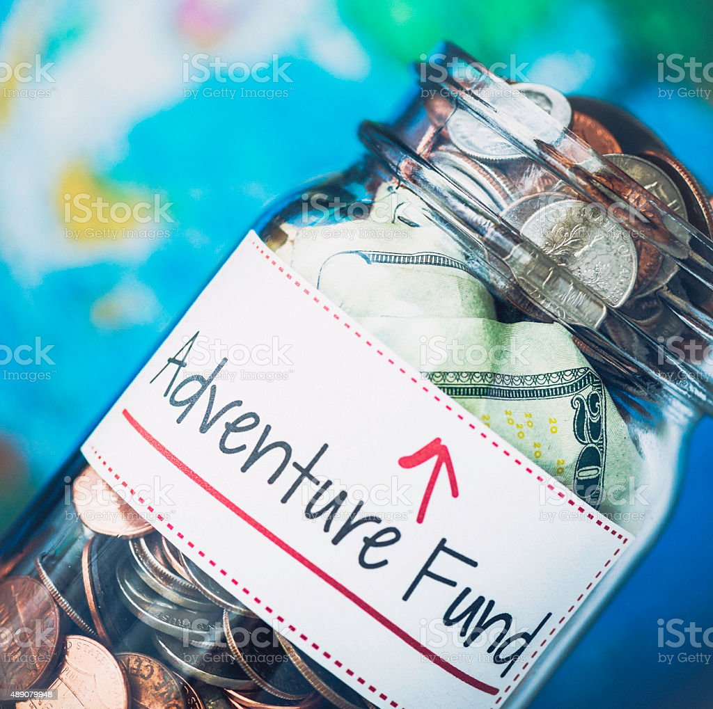 American money jar with Adventure Fund label and defocused globe stock photo