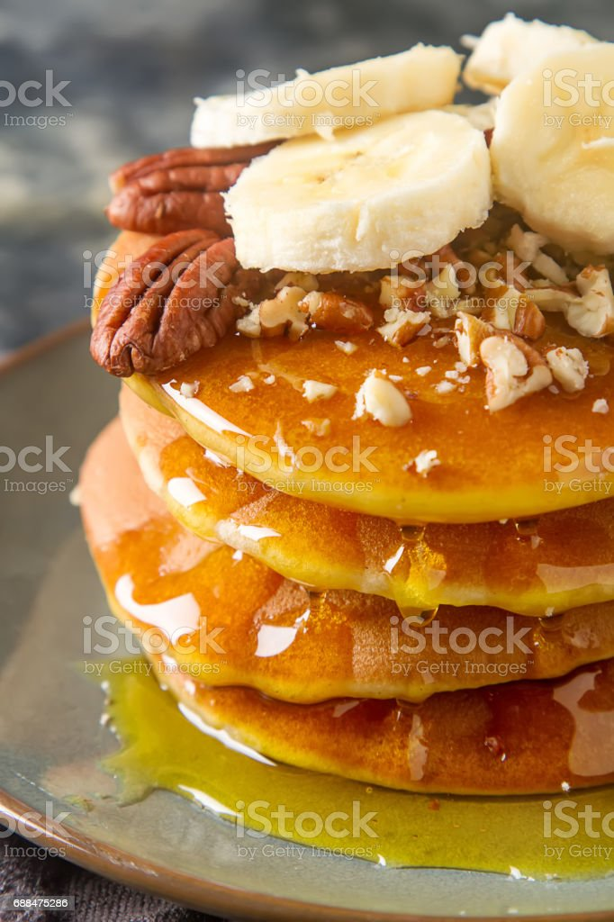 American pancakes on a plate with banana and nuts, sweet sauce. Dark background. stock photo