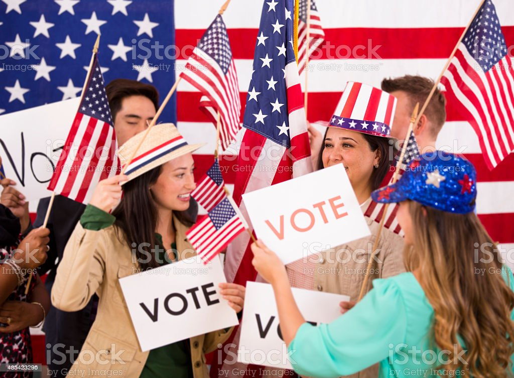 American people encourage voting. Political rally. USA flags. Vote signs. stock photo