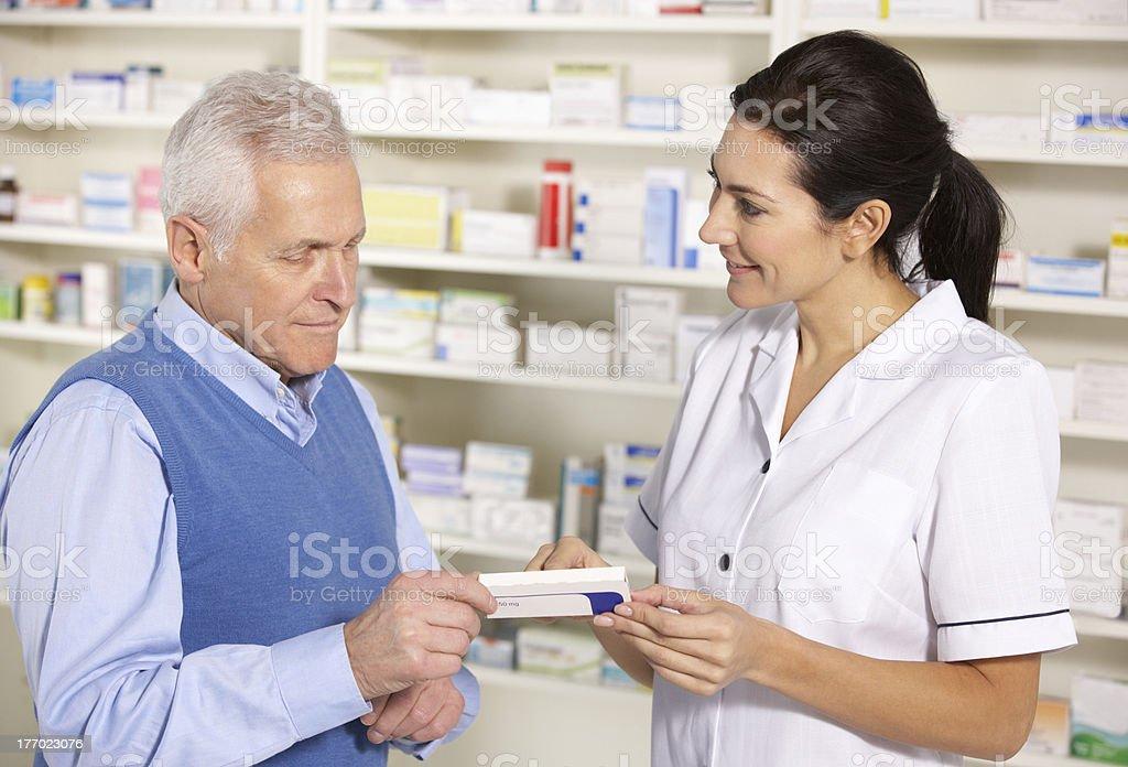 American pharmacist serving senior man in pharmacy royalty-free stock photo