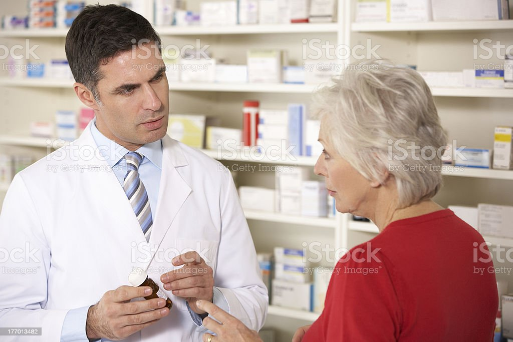 American pharmacist with senior woman in pharmacy stock photo