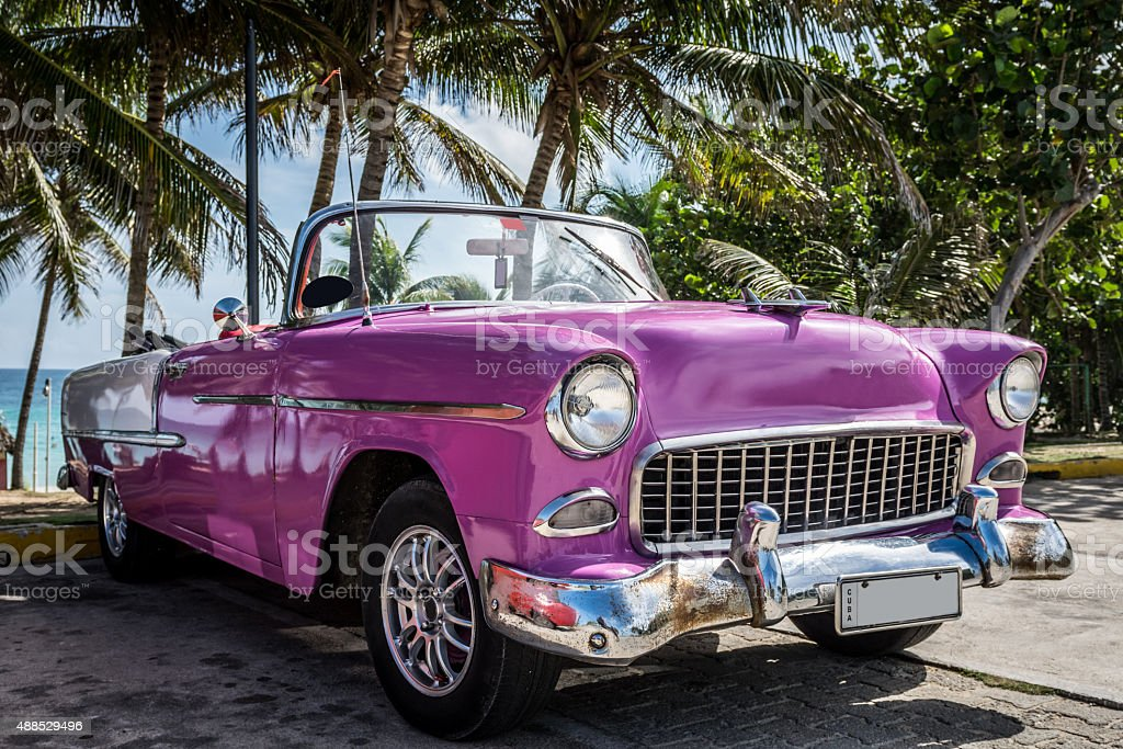 American pink vintage car near the beach in Cuba stock photo