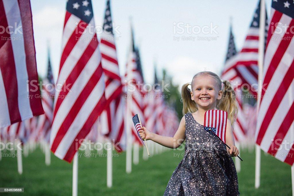 American preschooler running with American flag stock photo
