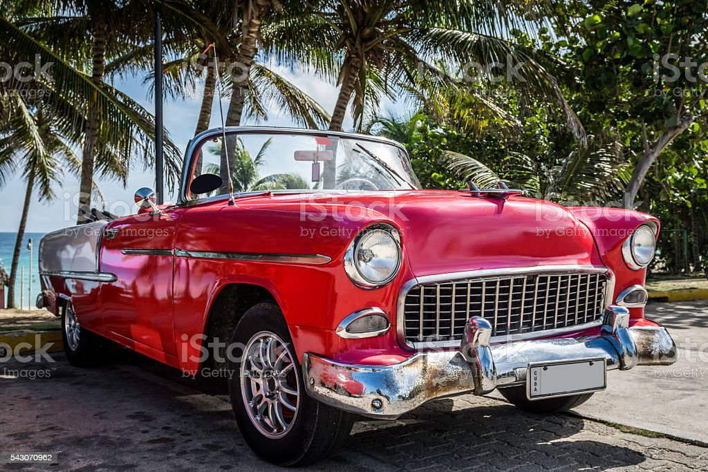 American red classic car parked under palms near the beach stock photo