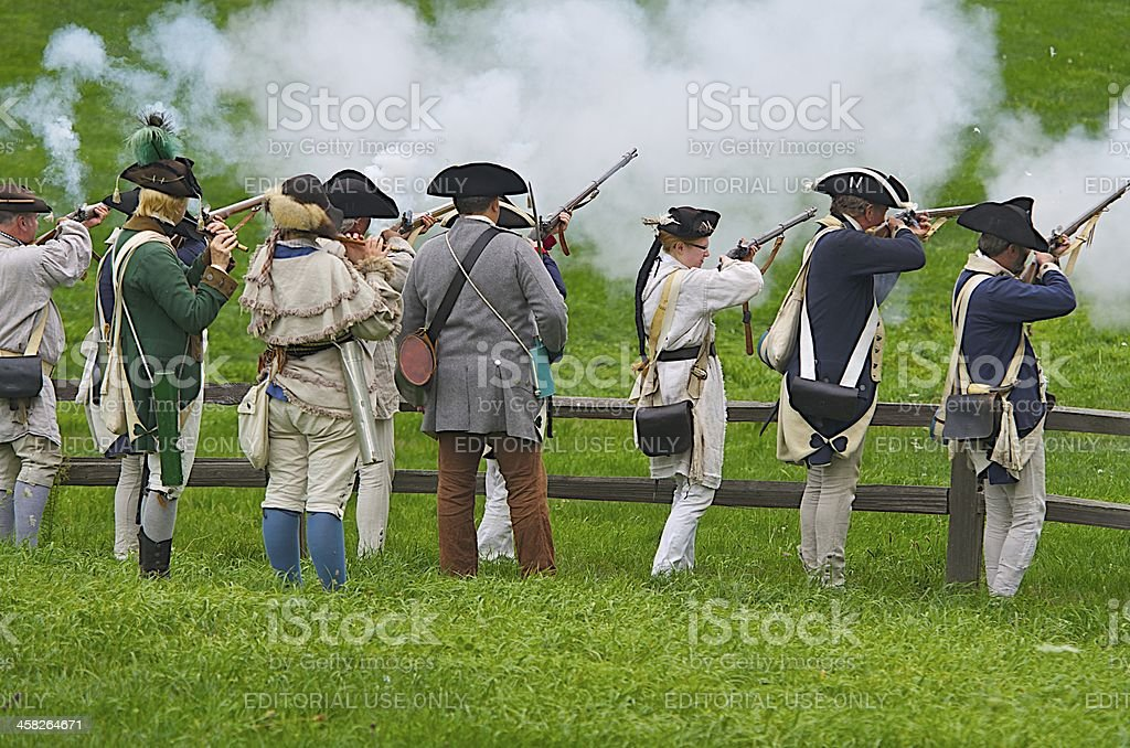 American Revolutionary war reenactors fire a musket volley stock photo