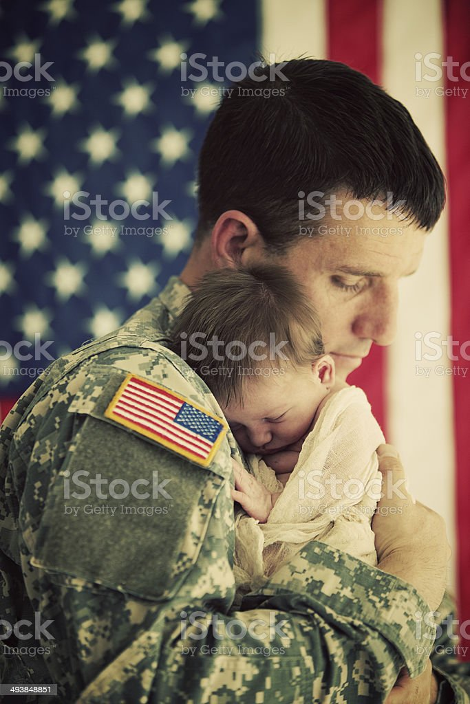 American soldier holding a newborn baby stock photo