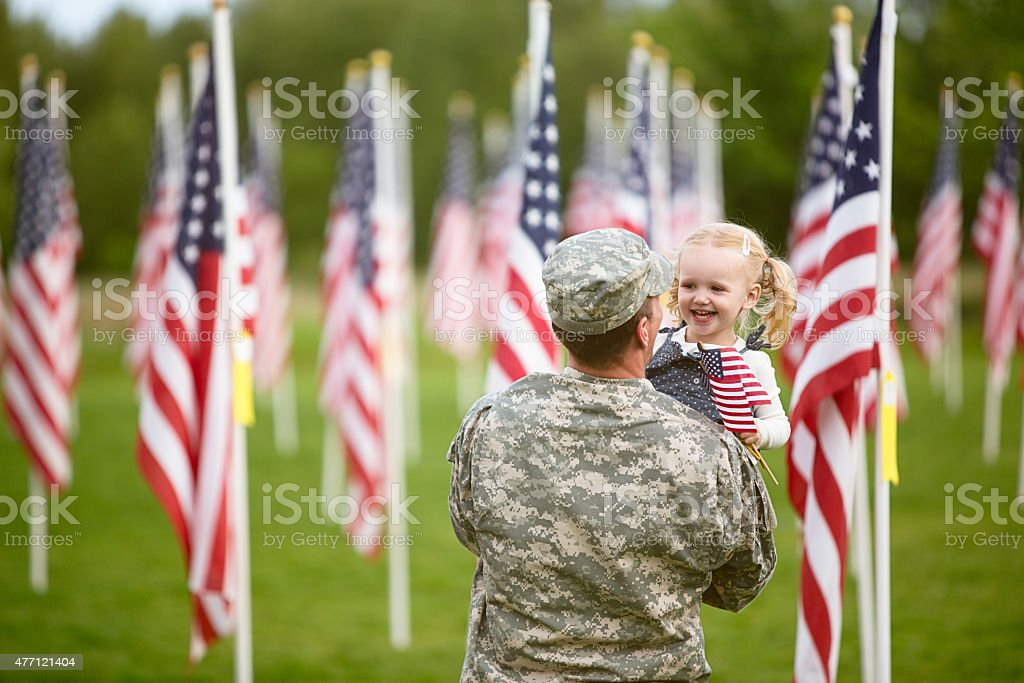 American soldier holding his happy toddler daughter stock photo