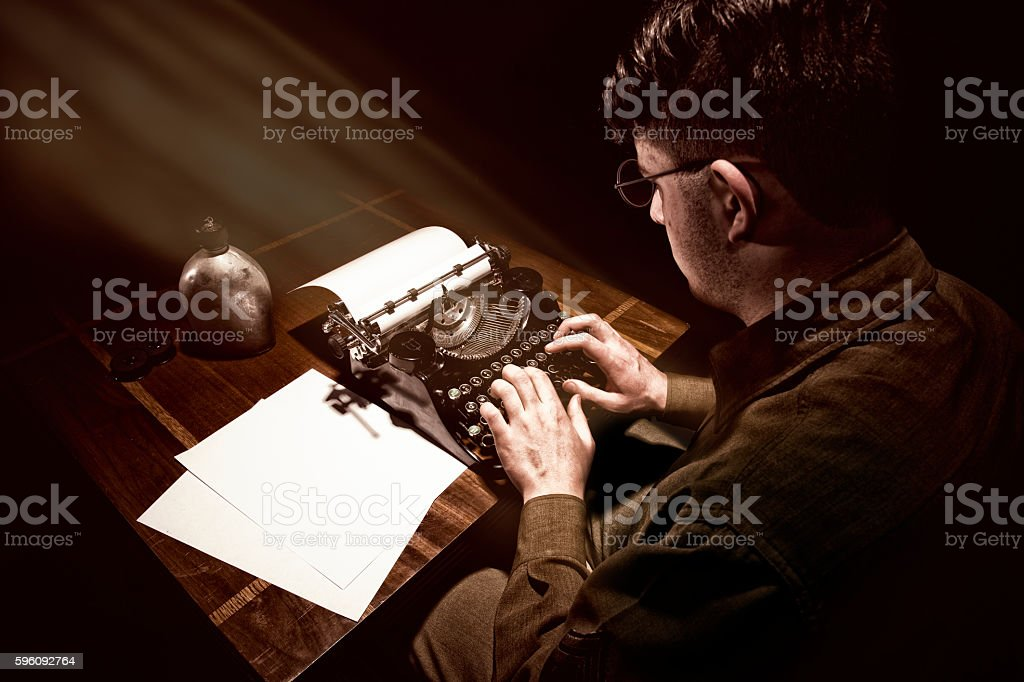 WWII American Soldier Sitting At His Typewriter Typing stock photo