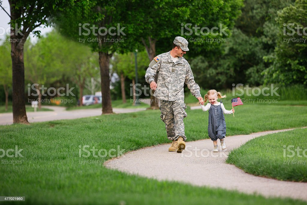 American soldier walking with his daughter stock photo