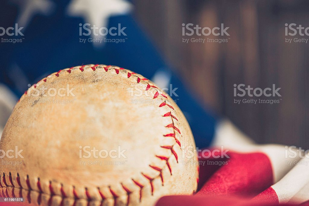 American sports. Worn softball with American flag and wood background