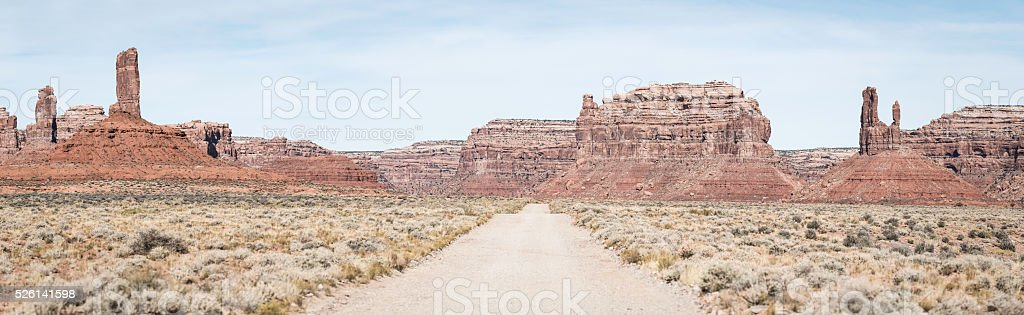 American West desert road through Monument Valley mesas pinnacles panorama stock photo