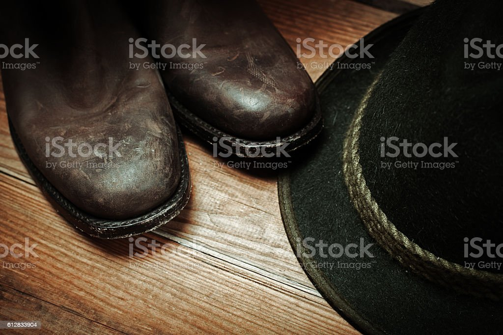 American West rodeo cowboy dirty and used brown botts and hat stock photo