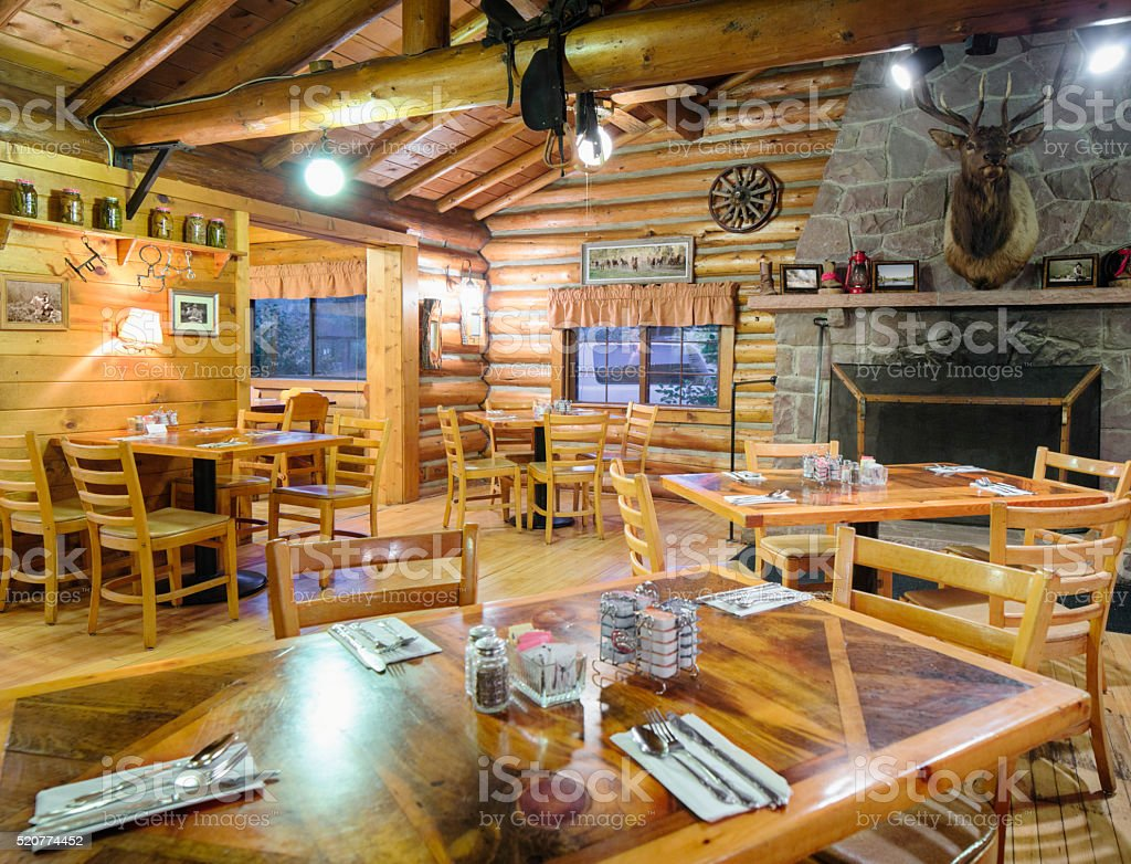 American Western log cabin restaurant dining room with fireplace stock photo