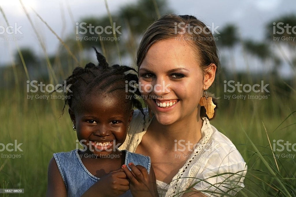 American Woman Holding African Girl stock photo