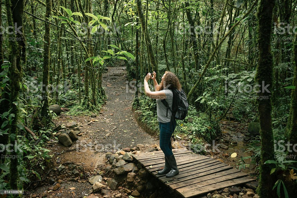 American Woman Takes Pictures on Hike in Costa Rica Rainforest stock photo