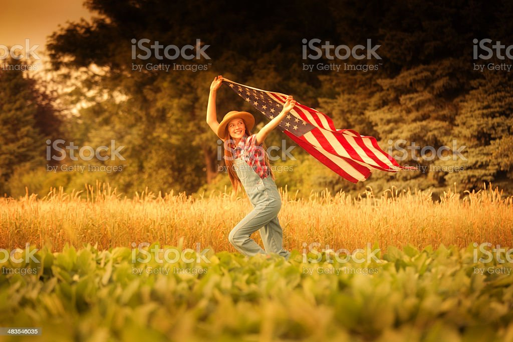Americana Farm Girl with U.S. Flag on 4th of July royalty-free stock photo