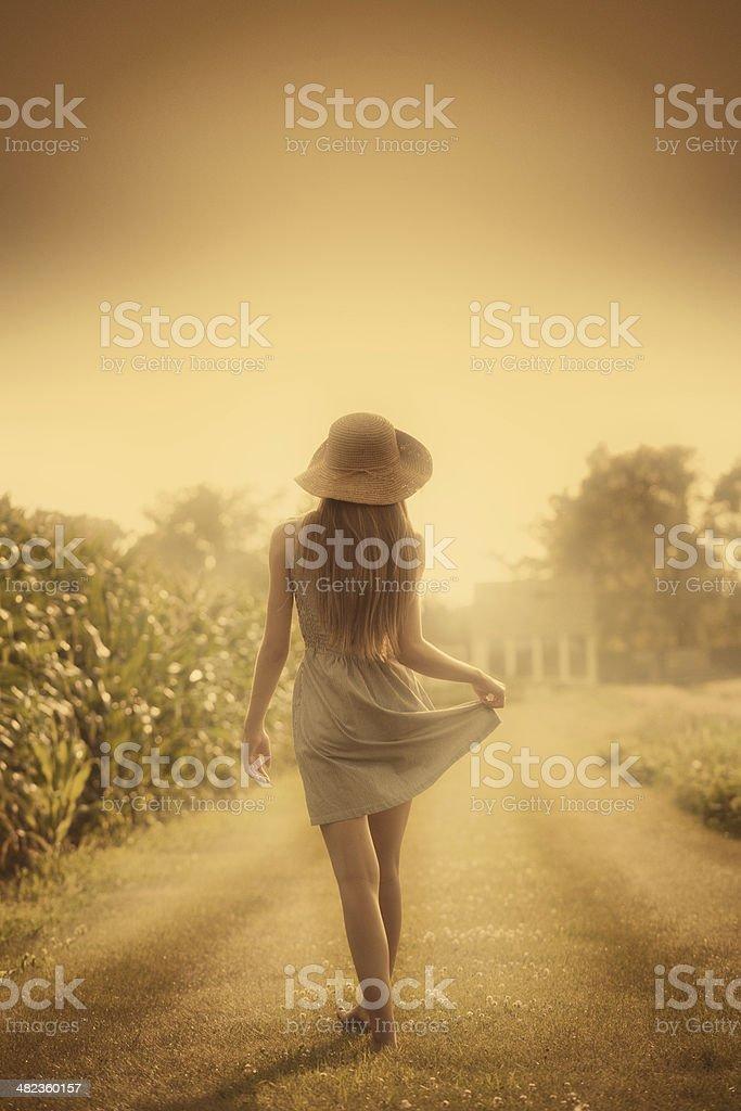 Americana Moment- Farm Girl Walking in Summer Field stock photo