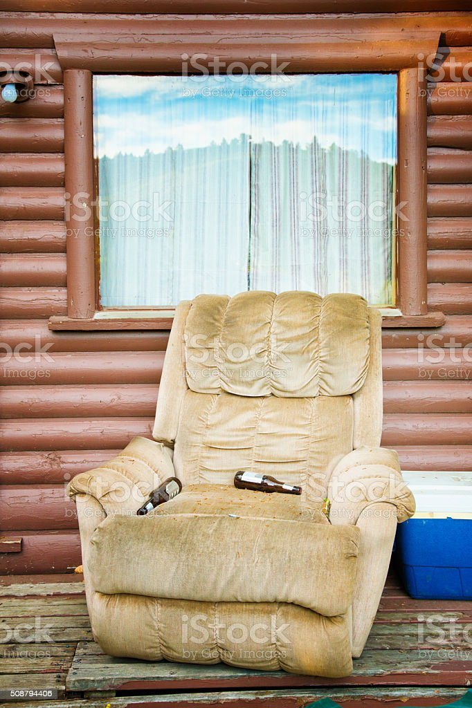 Americana: Recliner on cabin porch with beer bottles stock photo