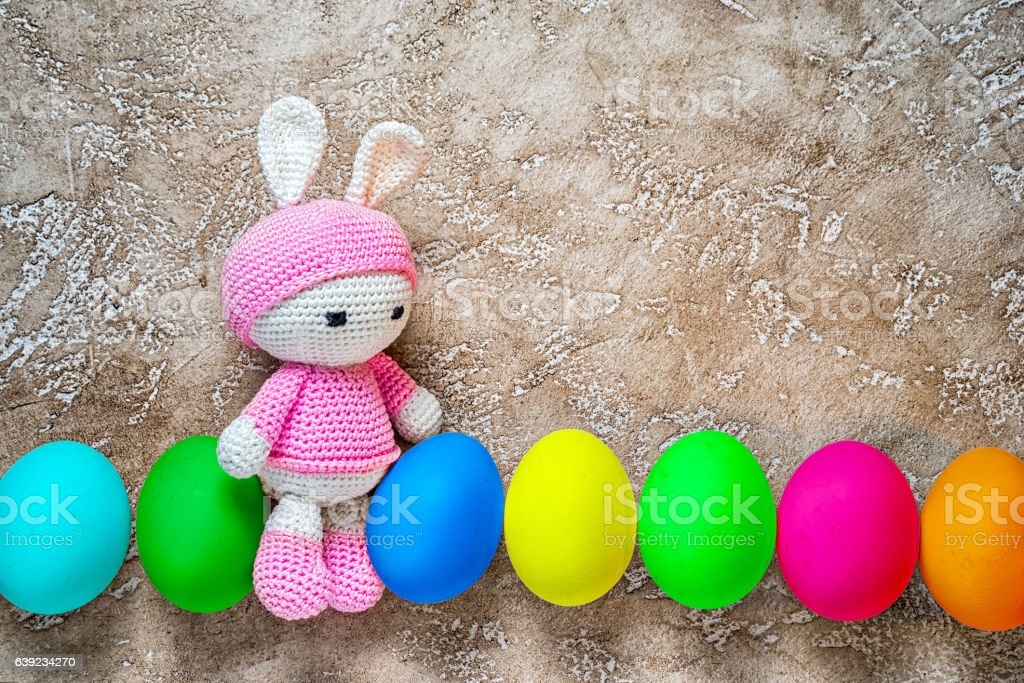 Amigurumi toy easter bunny with colorful eggs stock photo