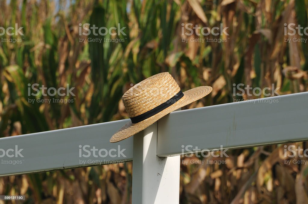 Amish straw hat laying over fence post stock photo