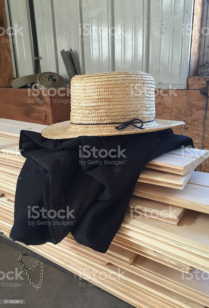 Amish Straw Hat Sitting on a Coat stock photo