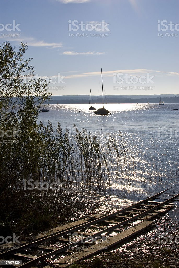 Ammersee with boat in the autumn and railroad tracks stock photo
